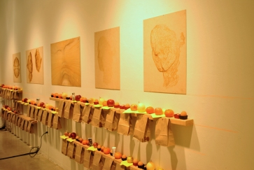 """From """"Stack and gather"""" by Greenmeme, opening night. The food is inspired by the idea of a pic-nic. The paper bag contain a vegetarian wrap, while above on the shelves are apples, pears oranges, hard-boiled eggs."""